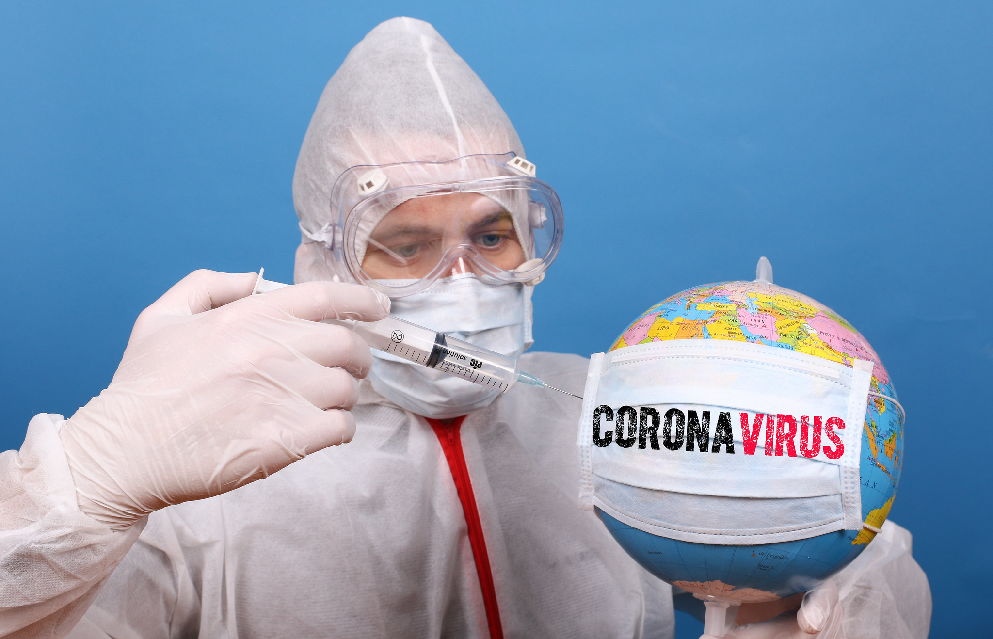 a man in an infectious disease suit injecting a globe with a vaccine